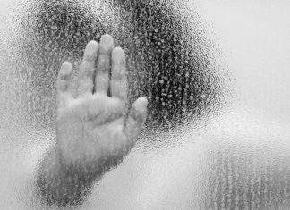 Kindermishandeling: hand achter glas van bang kind