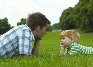 vader en zoontje liggend in het gras