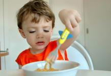 jongetje worstelt met bord spaghetti