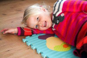 lachend meisje spelend op de grond
