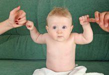 baby houdt vingers vader en moeder vast
